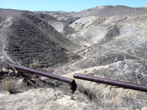 Half-buried and rusted pipelines crisscross these hills