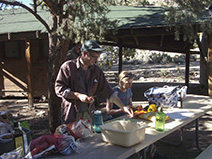 Richard and Franzi begin dinner preparations beside Charles Camp's cabin.