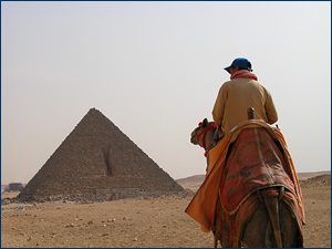A Bedouin tout selling camel rides in front of the 'Small' pyramid, Giza, Egypt