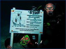 Two students pose with a sign meant to discourage recreational swimmers and snorkelers from entering the caves