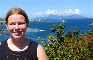 Molly on the island of Tahiti. That's Moorea with the clouds over it in the background