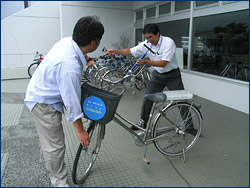 Curator Kumagai makes sure that Jann's rental bike has fully inflated tires