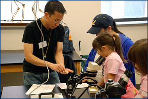 Drew Lee helps identify microfossils for a mom and daughter participating in UCMP's popular