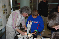 Museum scientist Diane Erwin shows a young visitor thin sections of petrified wood