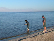 Zhaoxia Cui wades into the Salton Sea to collect foraminifera samples