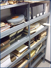 Shelves in the Type Room with a variety of archival materials