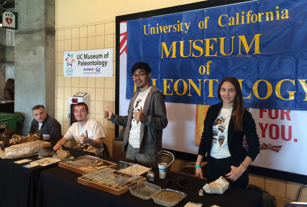 Graduate students (from left to right) Eric Holt, Nick Spano, Jun Lim, and Emily Orzechowski, prepare the exhibit table during Discovery Days at AT&T Park. Photo by Jun Lim
