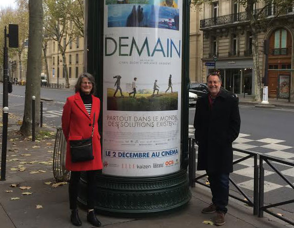 Tony and Liz by billboard advertising the movie Demain, in Paris.