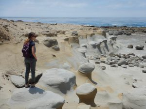 Emily standing on a concretion jutting out just below San Nicolas Island's youngest marine terrace (~80,000 years old).