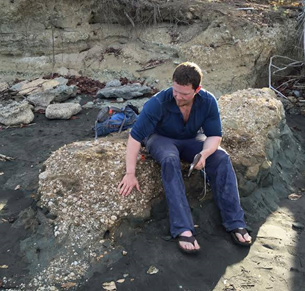 Larry Taylor in the field in Panama, getting ready to chisel a fossil whale barnacle out of the rocky outcrop he's sitting on.