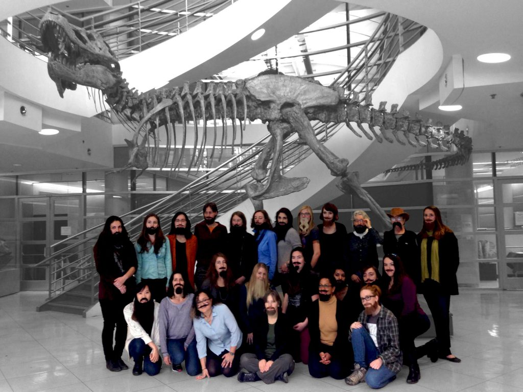 A group of women wearing fake beards pose in front the T-rex display at the Museum of Paleontology.